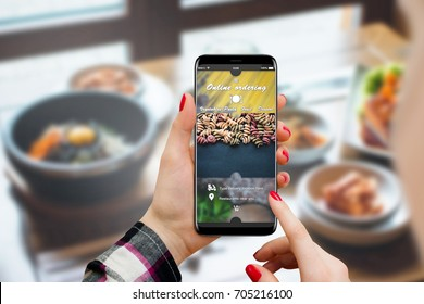 Girl ordering food online on her smartphone, restaurant in background