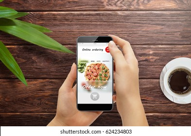 Girl ordering pizza online on smartphone, with table and coffee and plant in background