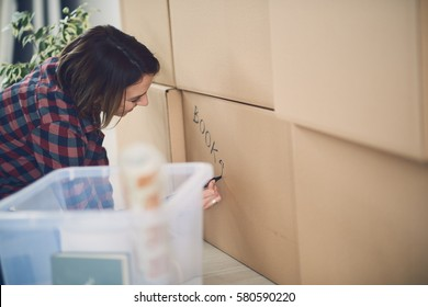 Girl organizes boxes in a new apartment