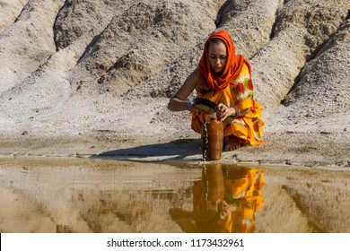 girl of oriental appearance in sari and hijab fills the pitcher with water from a dirty source in the arid area