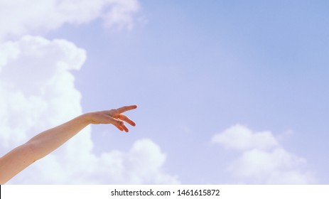 Girl outdoor against blue sky pointing with finger. Copy space text area.