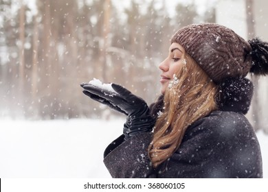 girl outdoor portrait. Winter woman blowing snow in a park, closeup