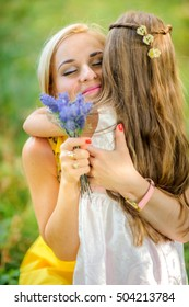 girl the outdoors, small bouquet of flowers, manifestation of tender feelings and care embrace mother, smile each other, a close-knit family, the relations of children and parents
