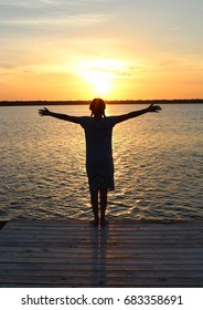 girl with outstretched arms in silhouette at sunset on lake
