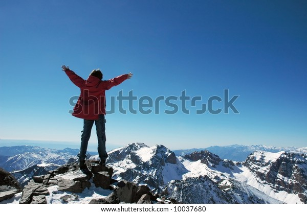 Girl over a snowcapped peaks with outstretched arms
