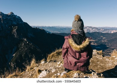 Girl overlooking Planica valley from a peak of a mountain in winter