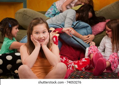 Girl overwhelmed with silly friends at a sleepover