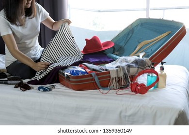 girl packing the luggage prepare for her journey trip with a lot of her cloth