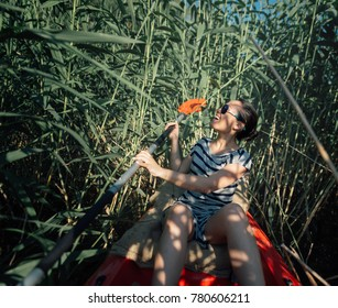 The girl with a paddle in a boat swam into a reed