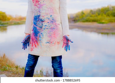 Girl in painted apron with dirty hands. Female artist outdoors.