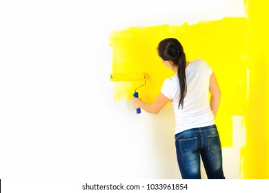 girl painter paints the walls with a roller, repairs in the house