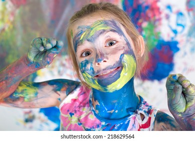 Girl painting with colors on her face