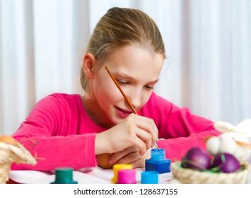 Girl painting an Easter egg