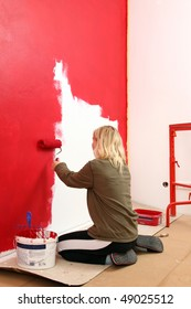 Girl painting living room in a red color.