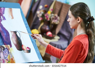 Girl painting still life by oil paint in studio