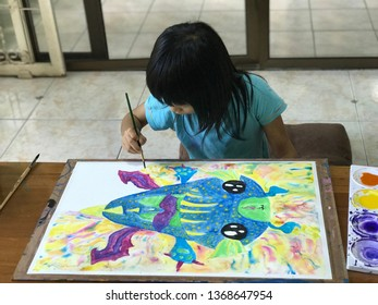 a girl painting water color on paper. Children drawing monster with her imagination and focus. Fully attention and concentrate. This is show child creativity and artistry skill