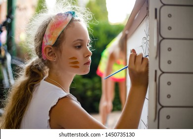 Girl paints a cardboard house at summer day, outdoor