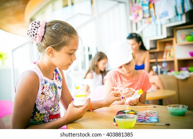 Girl paints clay toy, children's art, hobby summer, spend time on vacation, animation on holiday