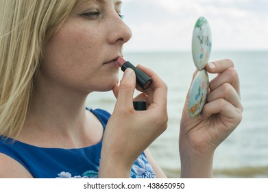 Girl paints her lips on the beach