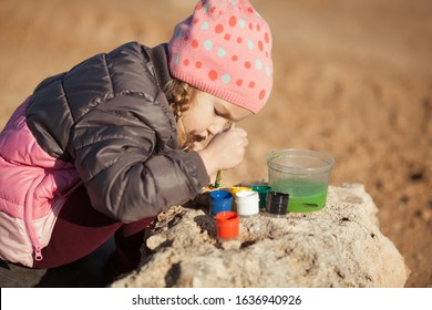 Girl paints pebbles on the seashore, outdoor