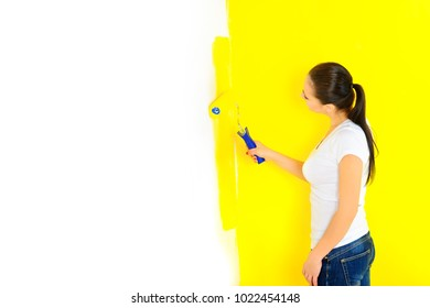 girl paints the walls with a roller, repairs in the house