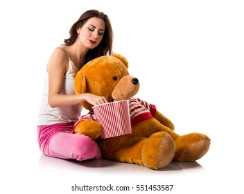 Girl with pajamas with a bowl of popcorns and playing with a stuffed animal