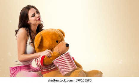 Girl with pajamas with a bowl of popcorns and playing with a stuffed animal on ocher background