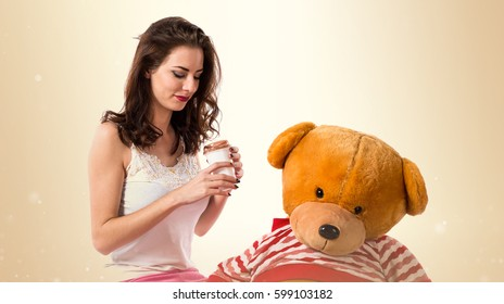 Girl with pajamas holding a take away coffee and playing with stuffed animal on ocher background