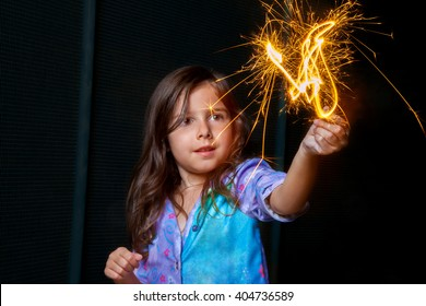 A girl in pajamas holds a burning sparkler up in the air while looking at it with wide eyes.