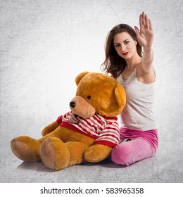Girl with pajamas making NO gesture on textured grey background