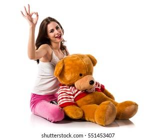 Girl with pajamas making OK sign and playing with stuffed animal