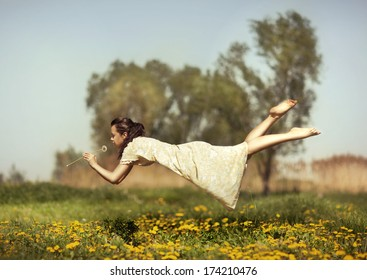 Girl in pajamas night flying over the field and smelling dandelions.