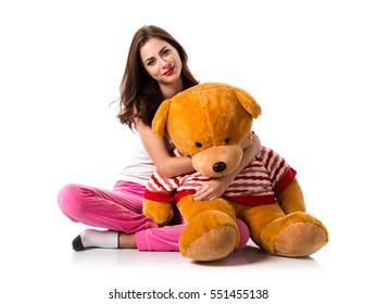 Girl with pajamas playing with a stuffed animal