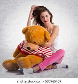 Girl with pajamas playing with a stuffed animal on textured grey background