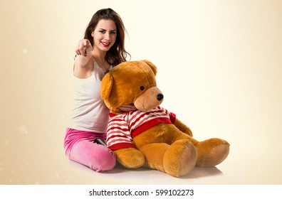 Girl with pajamas pointing to the front and playing with stuffed animal on ocher background