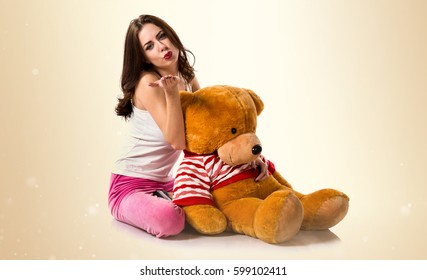 Girl with pajamas sending a kiss and playing with stuffed animal on ocher background