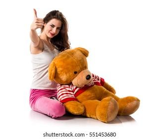 Girl with pajamas with thumb up and playing with stuffed animal