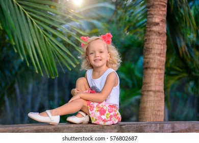 Girl in the palm garden in a nice dress