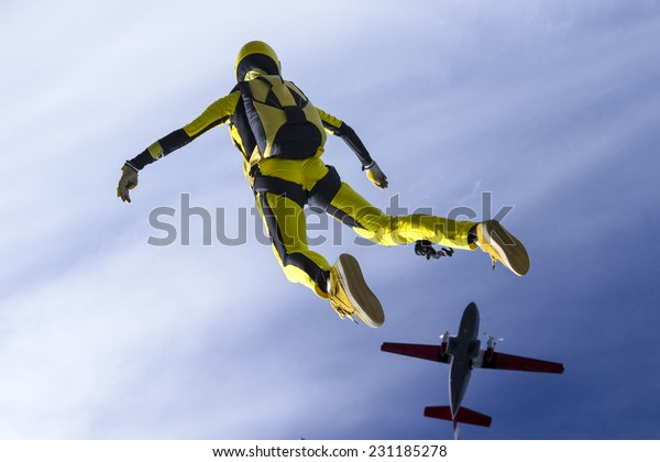 The girl parachutist jumps out of an airplane.
