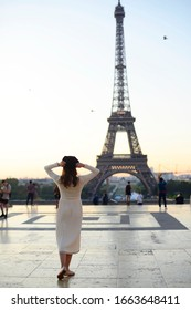 girl in Paris in a white dress against the background of the Eiffel tower elegant in the Trocadero square in summer luxurious beautiful figure of a Frenchwoman