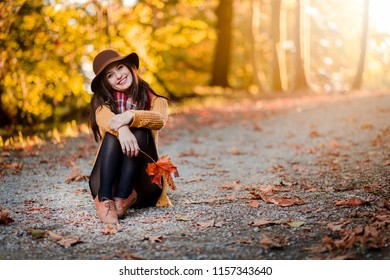 Girl in a park with autumn leaves around her