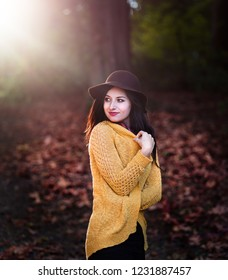 Girl in a park with autumn leaves around her.
