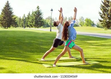 girl in park doing yoga with their teacher