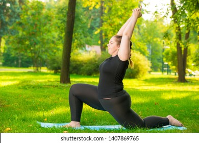 girl in the park is engaged in his figure, yoga exercises in the fresh air, model plus size