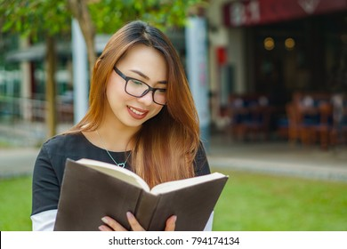 a girl in a park holding a book