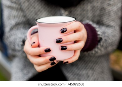 A girl in the park holding a cup of hot tea