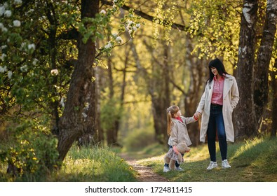 girl in the park holds mom by the hand and look at each other