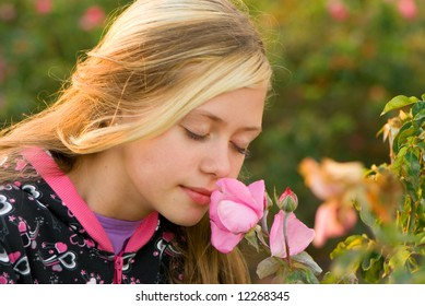 The girl in park of roses smells a rose