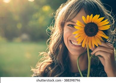 Menina no parque sorrindo e cobrindo rosto com girassol