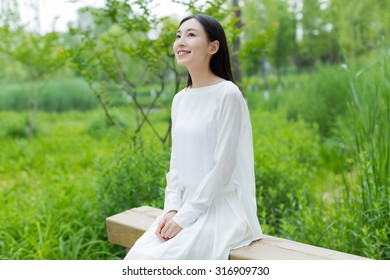girl in the park in a white dress on a sunny day